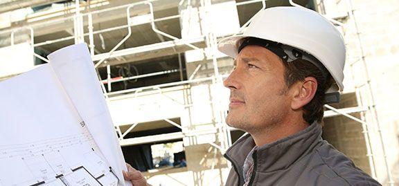 Homme sur un chantier avec casque tenant des plans